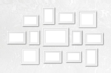 Photo frames collage, interior decor mock up, thirteen white frameworks on textured wall, gallery style.