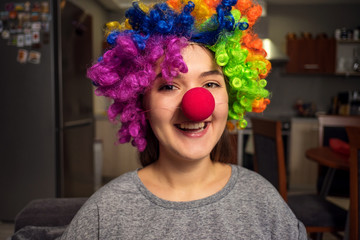 young woman in a clown wig preparing for holiday