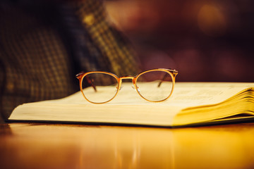 Golden luxury glasses on book lying on library table