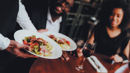 Waiter Serving Salad to African Couple Restaurant
