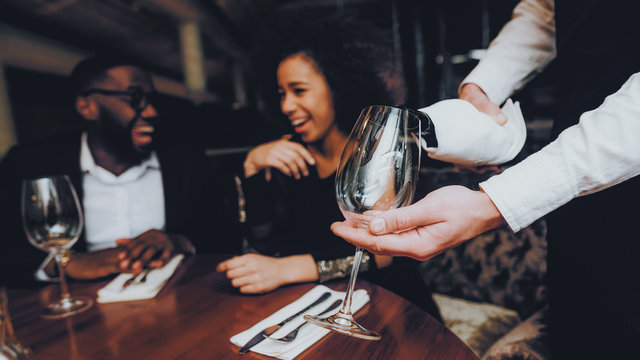 Waiter Pouring Wine to Glass Couple in Restaurant