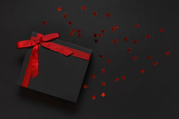 Black gift box with red ribbon and red holographic glitter confetti form of stars on dark background top view flat lay. Holiday concept, birthday gift, new year or Christmas presents Xmas holiday.