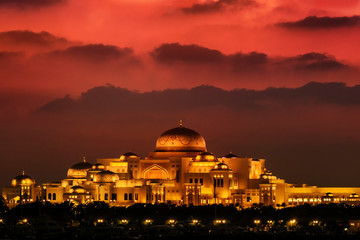 Beautiful sunset over the uae presidential palace in Abu Dhabi. The clouds look like mountains in the background.