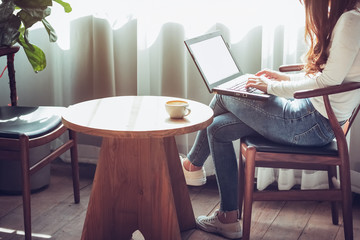 young business woman sitting near bright window use laptop working in retro cafe with coffee on wooden table