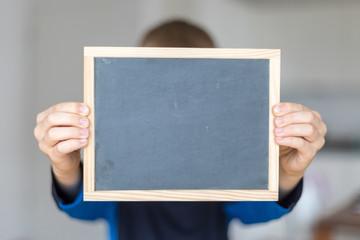 boy holding empty blackboard