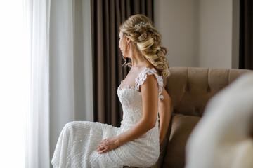 Beautiful blonde bride posing in luxury room
