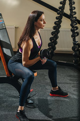 Fitness girl with on bench in the gym