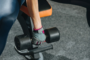 Close-up of woman lifts dumbbell to muscule in gym.