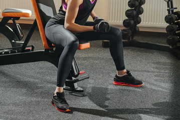 Woman lifts dumbbell to muscule in gym.
