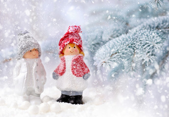 Christmas decorations little figure boy and girl on a background snow-covered fir branches. Christmas or New Year greeting card.