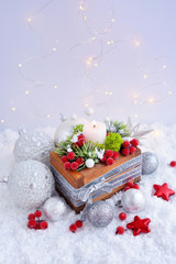 Christmas composition with a candle and festive decorations оn the snow. Christmas or New Year greeting card.