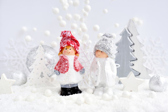 Christmas decorations little figure boy and girl with festive decorations оn the snow. Christmas or New Year greeting card.