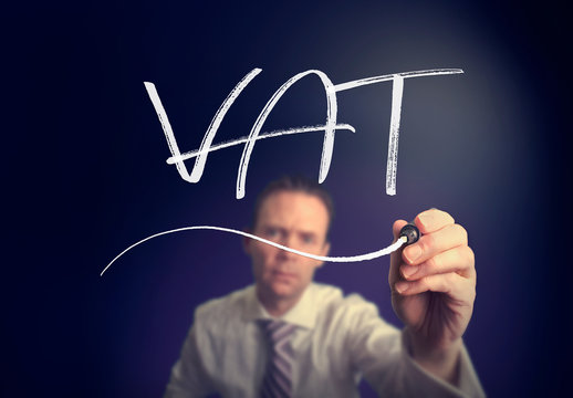 A businessman writing a VAT concept with a white pen on a clear screen.