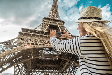 Woman tourist selfie near the Eiffel Tower in Paris under sunlight Fototapete