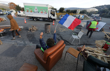 A protester wearing a yellow vest, the symbol of a French drivers' protest against higher diesel fuel prices, holds a French flag as he occupies with comrades a roundabout in Nice