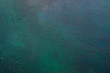 Dark green-blue painted wooden background.