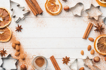 Ingredients for making Christmas cookies. Rolling pin cookie cutters cinnamon cocoa nuts on a light background with copy space.