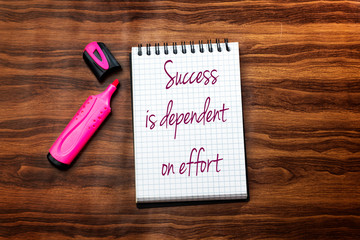 Success Is Dependent On Effort  text writing in notebook . Concept meaning Make effort to Succeed Stay Persistent