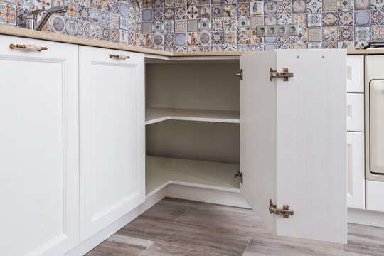 Solution for a kitchen corner in a cupboard. The angular opening with corner hinges. Classical kitchen interior, white wooden fronts and thin quartz countertop.