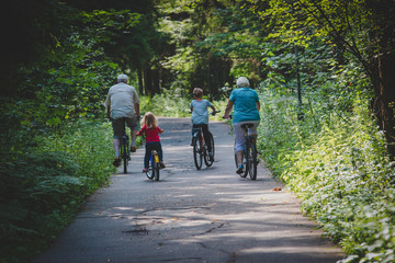 active senior grandparents with kids riding bikes in nature