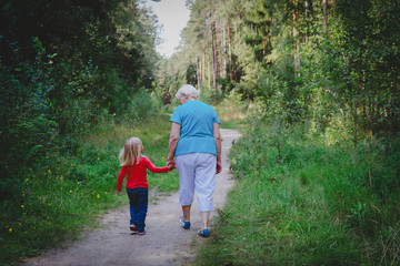senior grandmother with little granddaughter walk in nature