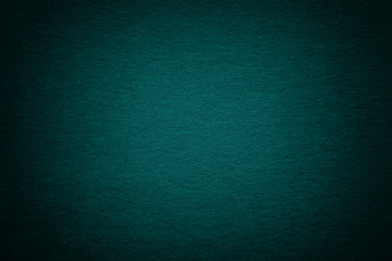 Texture of old dark turquoise paper background, closeup. Structure of dense deep bluish cardboard.
