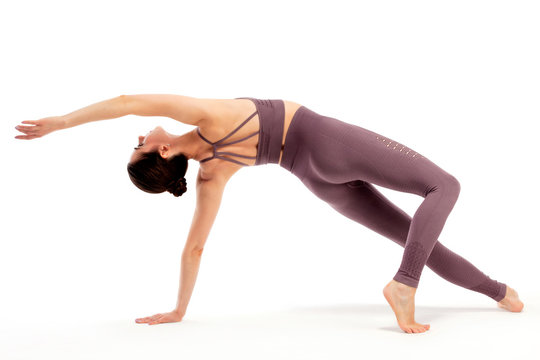 Young beautiful yoga woman is posing in studio on white background