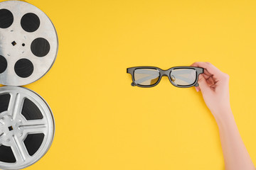 film reels and female hand holding stereoscopic 3d glasses isolated on yellow