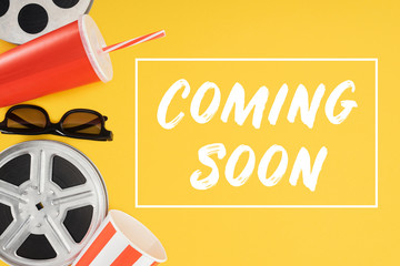 """film reels, 3d glasses, popcorn bucket, red disposable cup with straw and """"coming soon"""" lettering isolated on yellow"""
