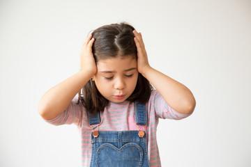 Tired Hispanic child having headache. Upset Latin preschooler kid with closed eyes. Isolated on white. Headache concept