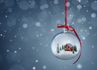 Cozy christmas gingerbread house in glass ball over gray background with copy space