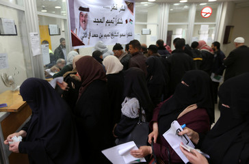 Palestinian Hamas-hired civil servants wait to receive their salaries paid by Qatar as a banner showing a picture of Qatar's Sheikh Tamim bin Hamad Al Thani is seen, in Khan Younis in the southern Gaza Strip