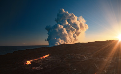 Kilaulea volcano lawa flow, steam cloud rising from ocean at sunset time