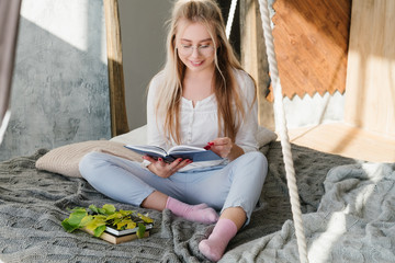 young woman reading book sitting at home. comfy relaxed leisure