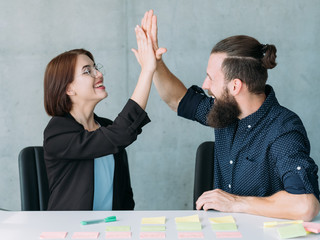 man and woman giving high five sitting at table in office. teamwork success and cooperation
