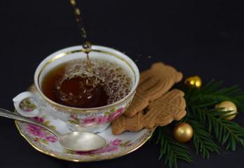 Tasse Tee in einer eleganten Porzellantasse mit Silberlöffel, Spekulatius-Plätzchen, Tannenzweigen und goldenen Christbaumkugeln vor dunklem Hintergrund