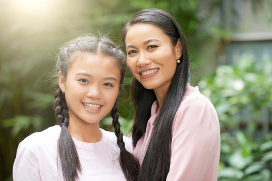 Beautiful adult Asian woman with charming teenage girl smiling at camera in sunlight