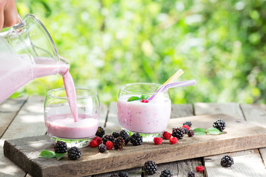 Berry smoothie or yogurt pouring from jug into glass