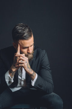 Young man wearing suit, sitting with worried expression, tattoos on hands