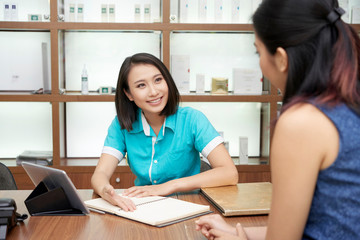 Charming Asian woman working in spa salon at reception and talking to client friendly