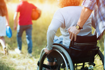 Close up look on woman's back in a wheelchair.