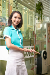 Smiling young Asian woman in uniform welcoming into spa salon looking at camera