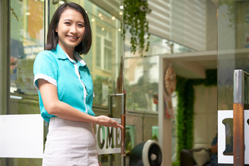 Beautiful Asian brunette greeting guest at glass doorway of spa studio and smiling at camera