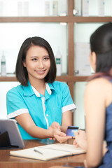 Young Asian receptionist in spa salon taking credit card of guest while smiling
