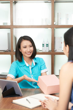 Cheerful Asian worker of spa salon giving gift box to young client at counter