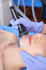 Crop shot in closeup of spa salon master pampering skin of young woman with electronic tool