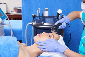 Side view of relaxing Asian woman lying on table and enjoying soothing face procedure with professional equipment
