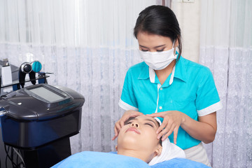 Asian woman in mask massaging face of pretty young client lying on table in spa salon
