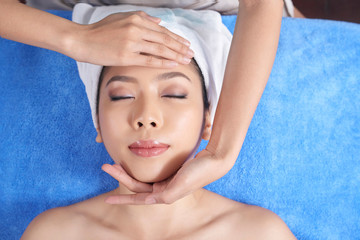 From above shot of crop master giving tender massage to young Asian woman lying on blue towel
