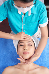 From above shot of Asian woman lying on towel in spa salon having tender face massage